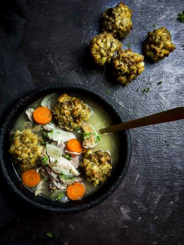bowl of soup with carrots and stuffing dumplings