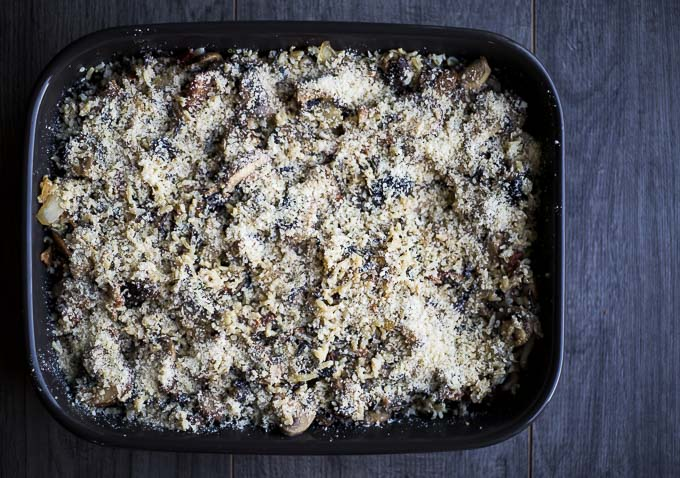 baking dish with wild rice stuffing covered in parmesan cheese, uncooked