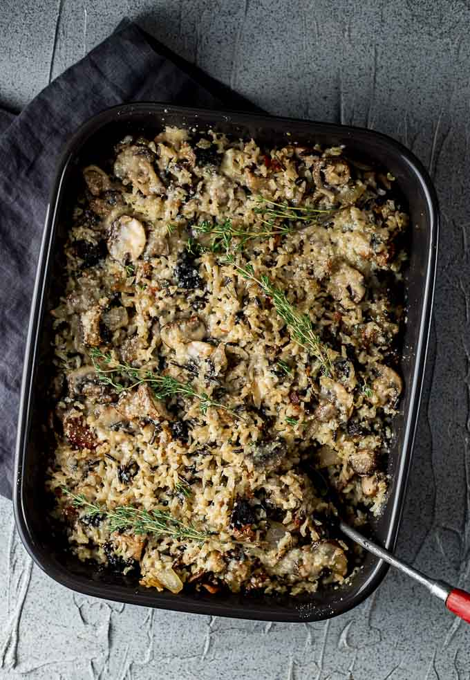 wild rice stuffing in a baking dish with fresh thyme