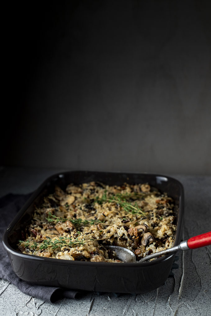 baking dish of wild rice and mushroom stuffing with a serving spoon