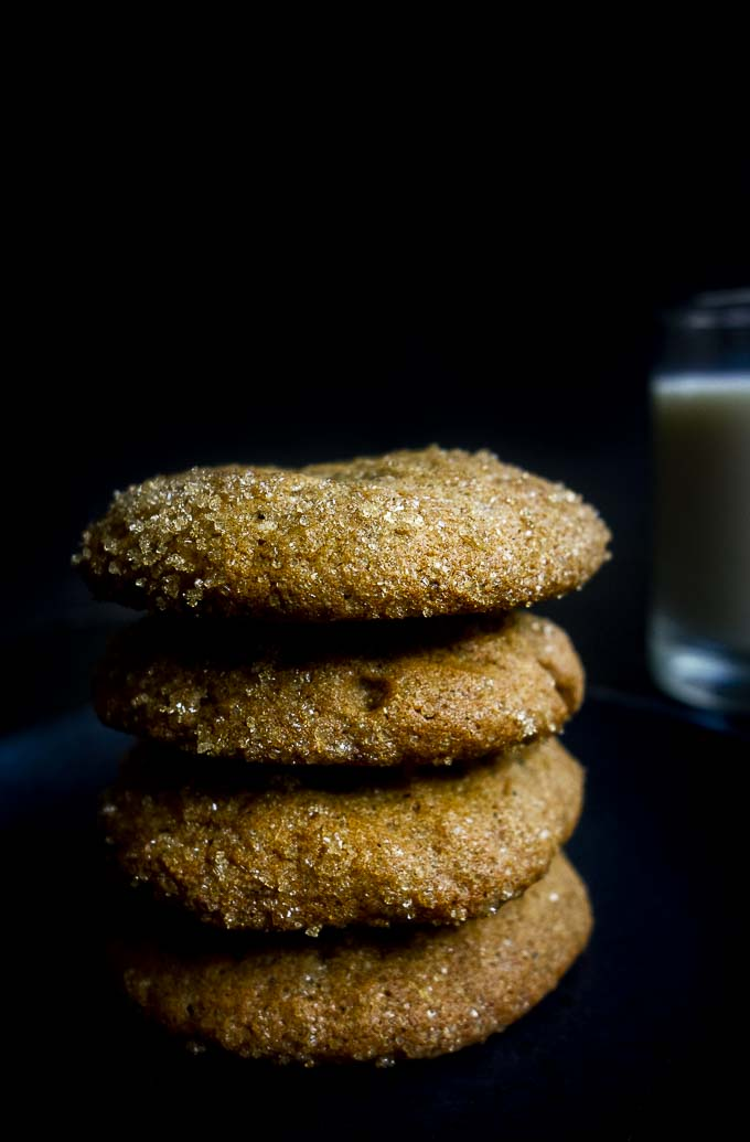a stack of molasses cookies with milk in the background