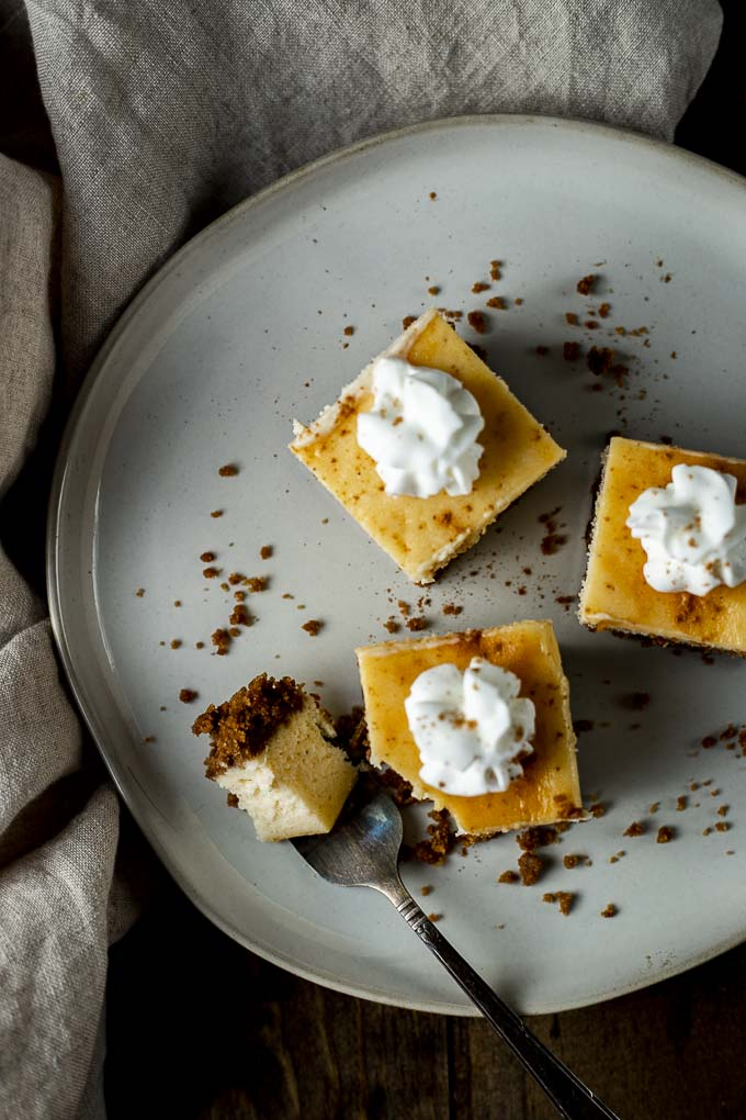 3 eggnog cheesecake bars on a plate with a fork
