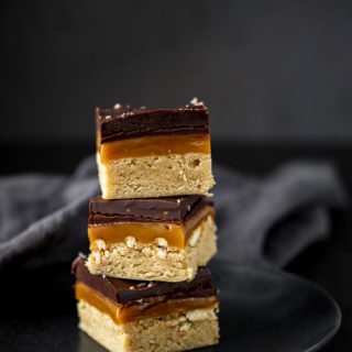 millionaire shortbread bars in a stack (shortbread, caramel, chocolate layers)