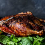 side view of a crispy roasted duck