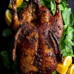 whole roasted duck on a platter
