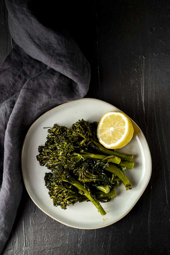sauteed broccolini on a plate with a lemon