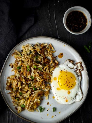 crispy hash browns with an egg and green onions