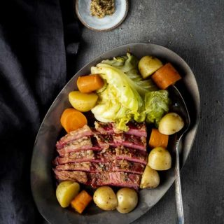 a plate of corned beef and cabbge with potatoes and carrots and mustard on the side