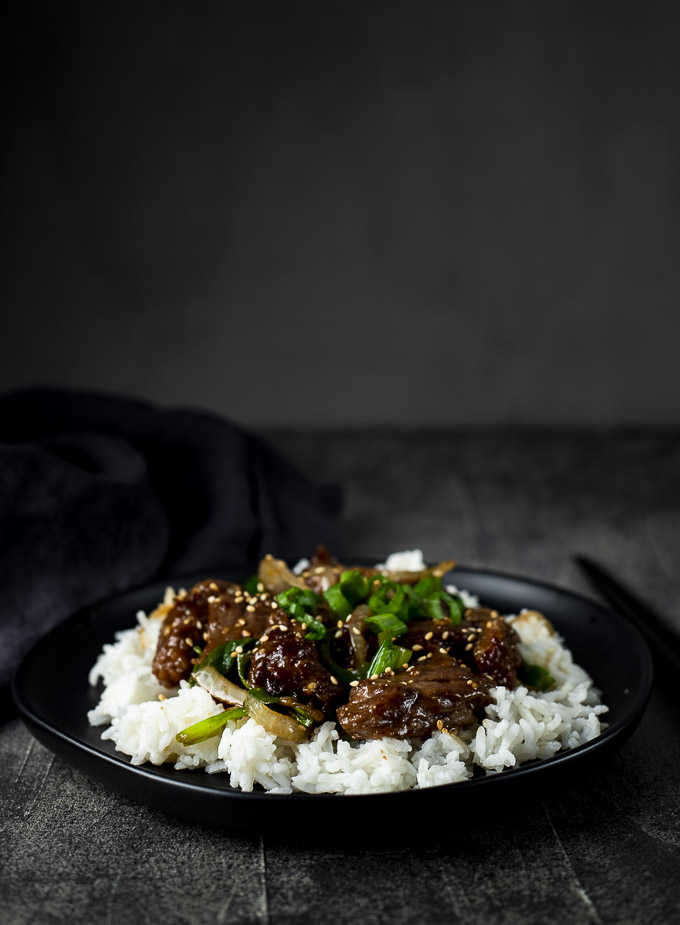 beef in sauce on a plate with green onions