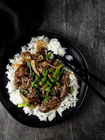 mongolian beef over rice on a plate with chopsticks