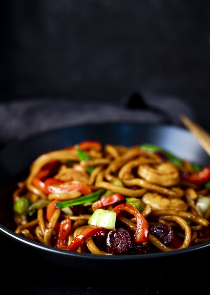 shrimp lo mein with veggies and sausage in a bowl