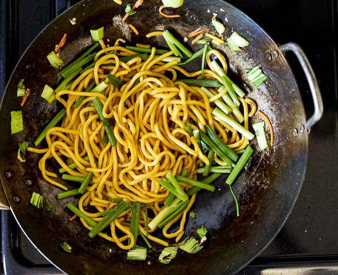 noodles and green onions in a wok