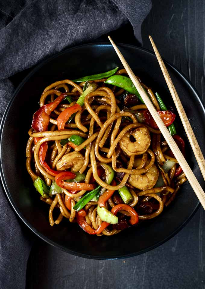 shrimp lo mein in a bowl with chopsticks