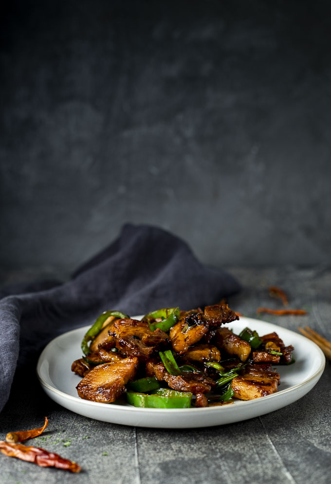 stir fried pork on a plate with green chilies