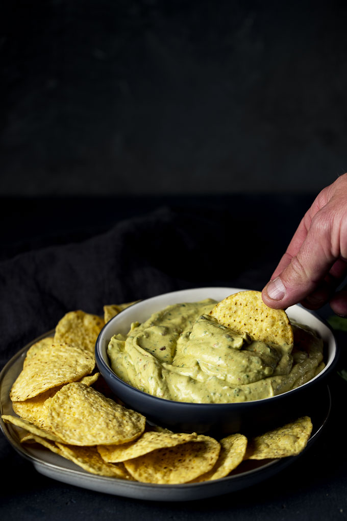a chip being dipped into a bowl of avocado dip