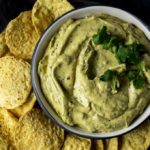 a bowl of avocado dip with chips on the side