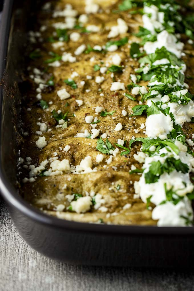 enchiladas topped with sour cream in a baking dish