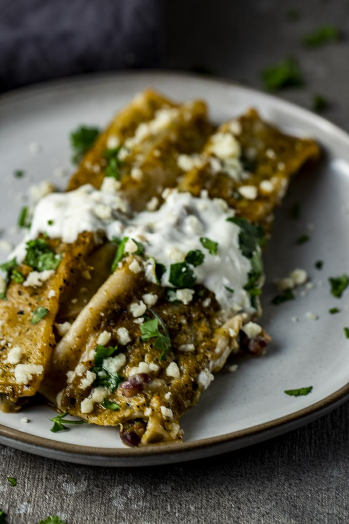 2 enchiladas on a plate with sour cream and cilantro
