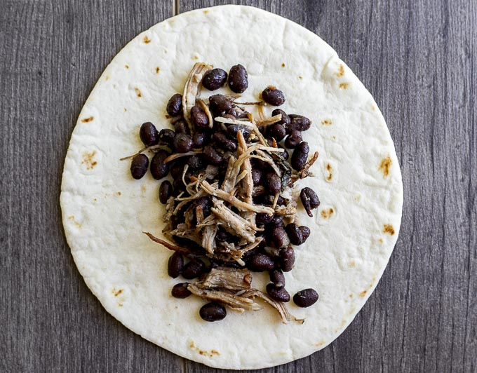 pork and black beans on a tortilla