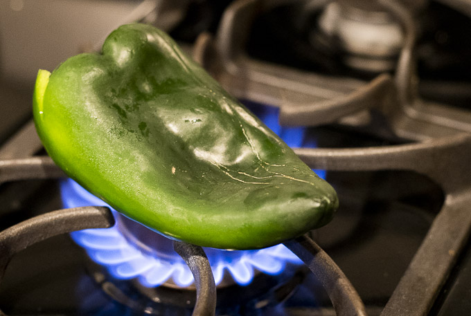 fresh poblano pepper over a gas stove
