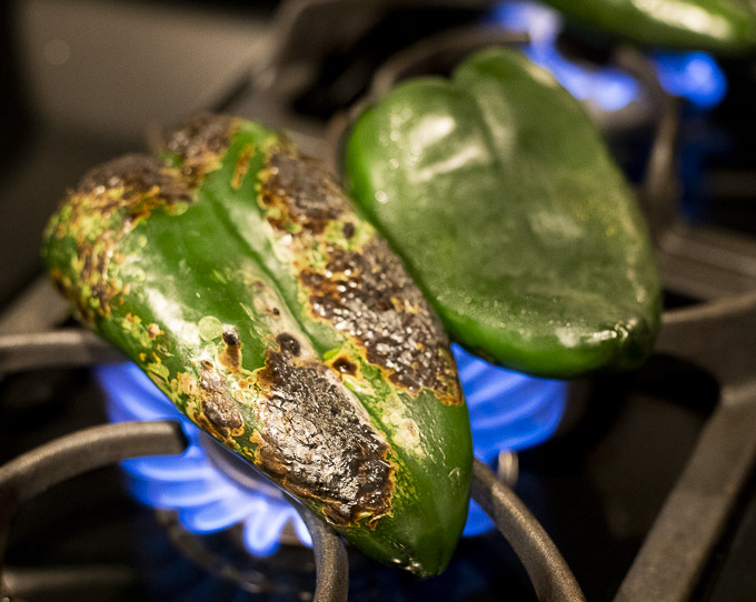 poblano pepper being roasted on a gas burner