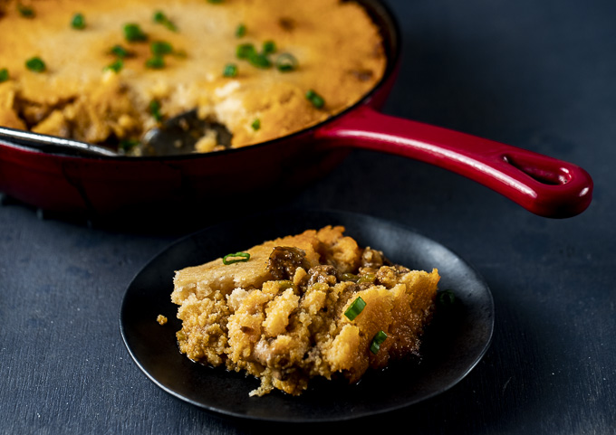 piece of tamale pie on a plate with skillet in the background