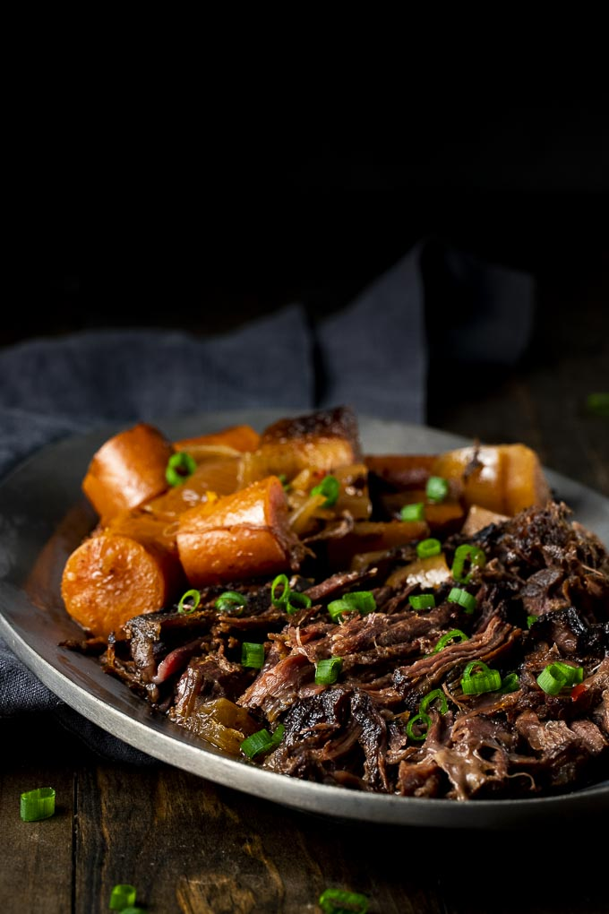 shredded beef and carrots on a plate with green onions