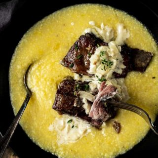 beef short ribs in a bowl of polenta with cream sauce