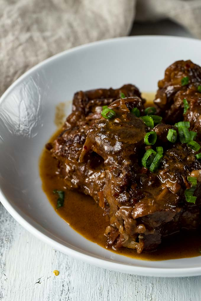 braised oxtails on a bowl with sauce and green onions