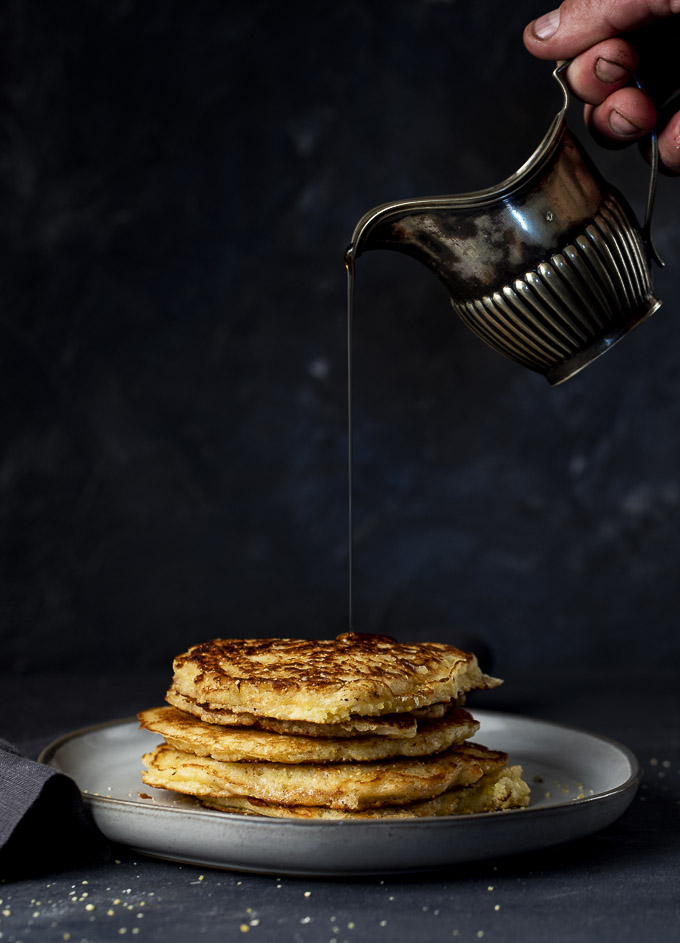 stack of cornmeal pancakes with syrup being poured on