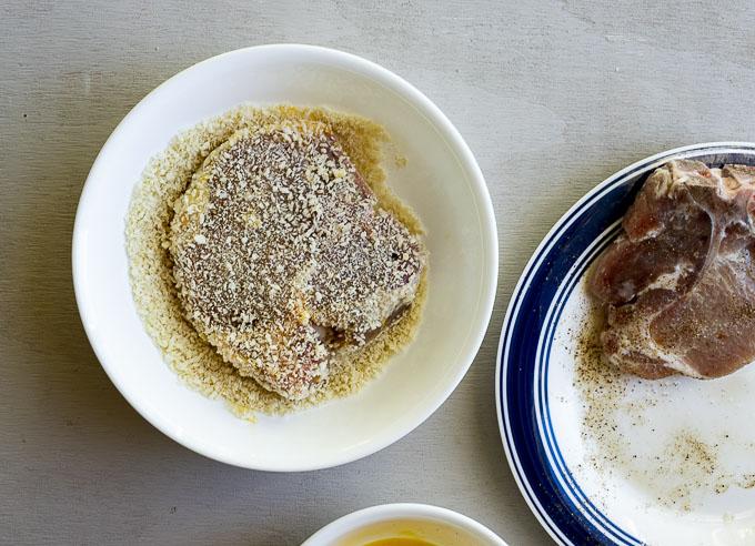 pork chop being dipped in bread crumbs