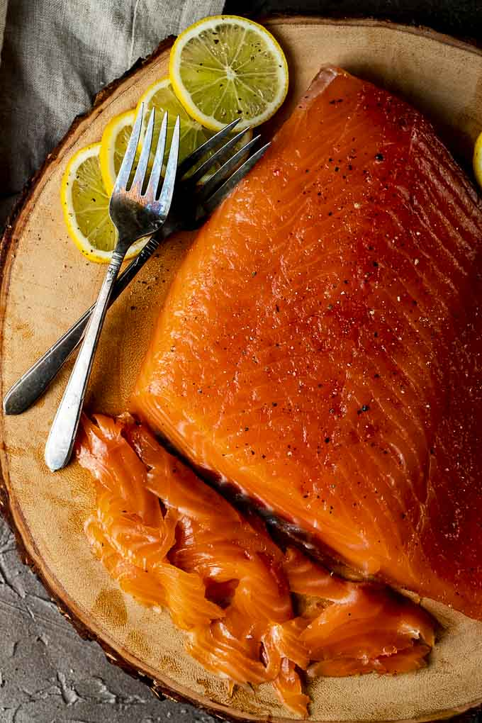 sliced cured salmon on a platter with lemon slices