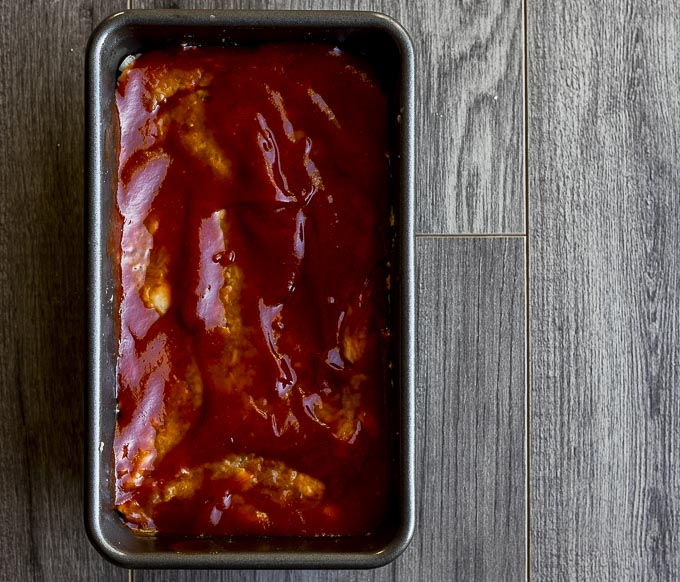 raw meatloaf covered in ketchup sauce