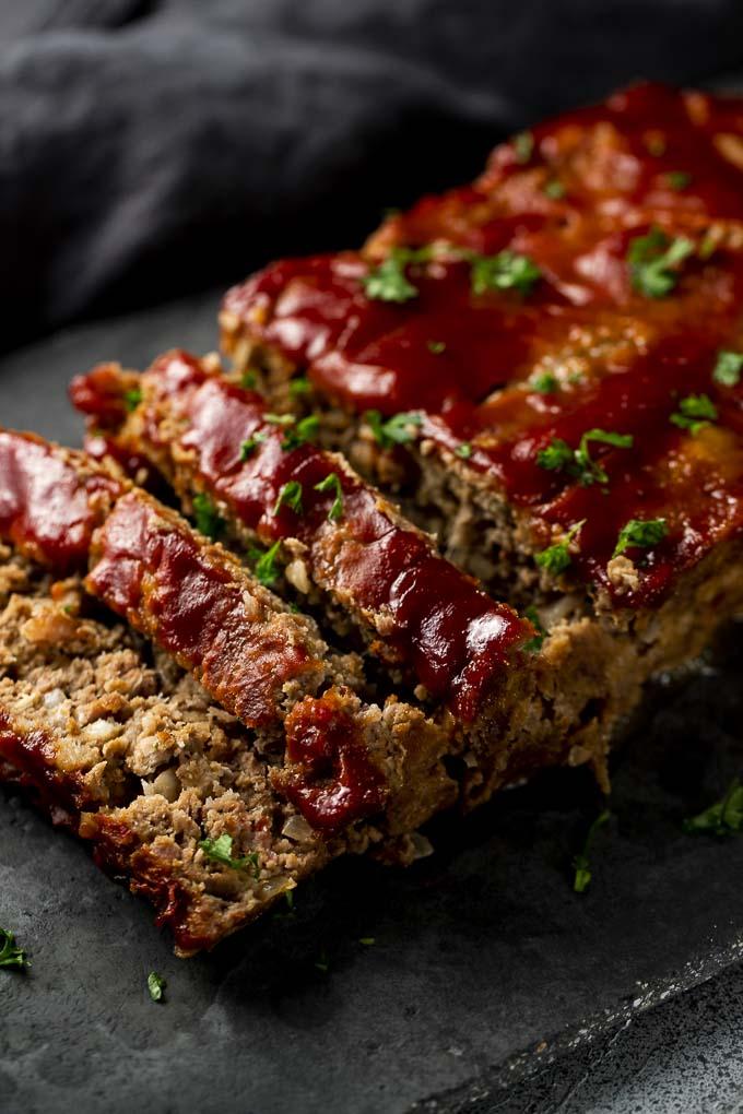 ketchup sauce covered meatloaf slices on a platter