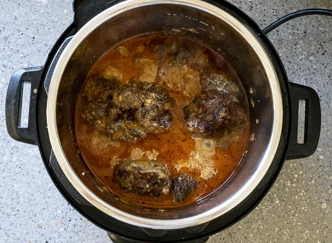 oxtails simmering in orange sauce