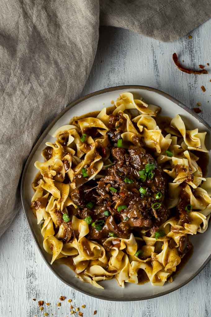 braised oxtail on a plate over egg noodles