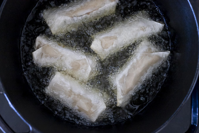 egg rolls being fried in oil