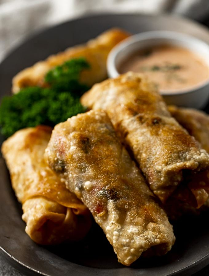 plate of fried egg rolls with orange sauce and pasrley