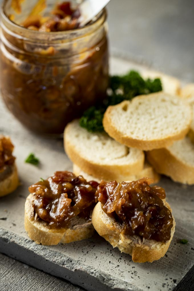 a plate of sliced baguettes with a jar of jam