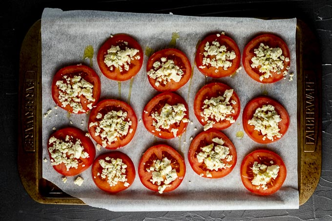 raw tomatoe slices covered in crumbled cheese on parchment paper