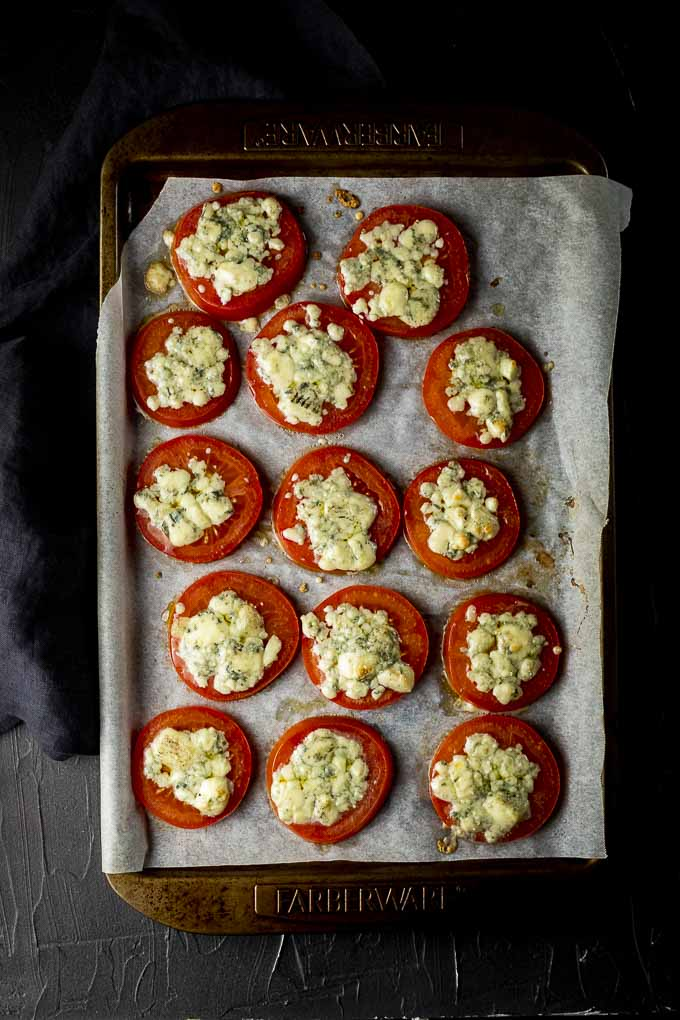 broiled tomatoes covered in cheese on a baking sheet