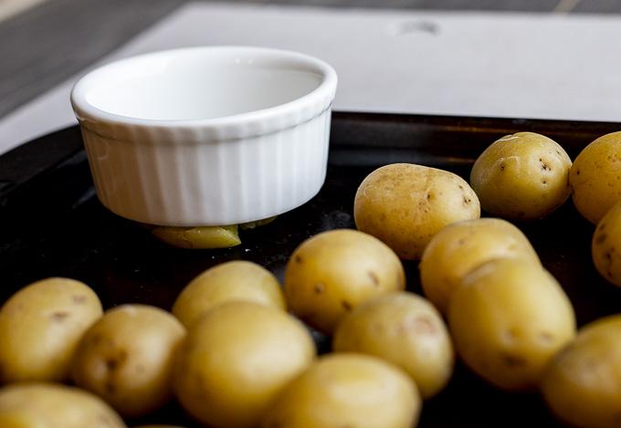 mini potatoes on a trash being smashed with a ramekin