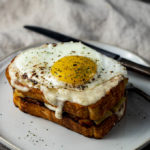 egg topped sandwich with sauce