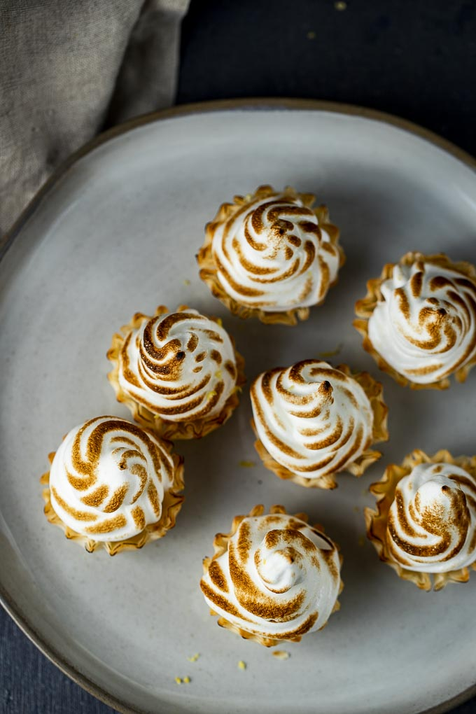 meringue topped lemon tarts on a plate