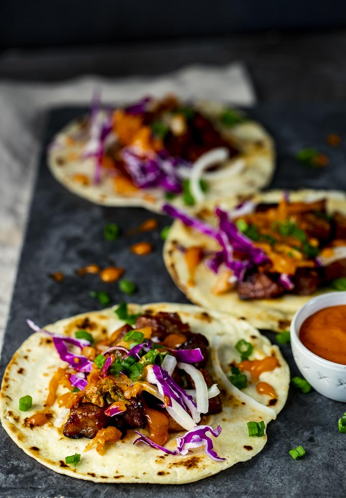 plate of 3 tacos with red cabbage and green onions