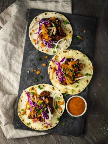 3 flat tacos on a plate with orange sauce on the side