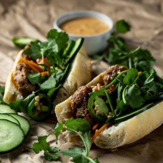 2 meatball sandwiches with herbs and vegetables on a baguette