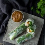 summer rolls with one halved on a plate with brown dipping sauce
