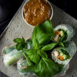 summer rolls with chicken and vegetables on a plate with herbs and dipping sauce