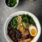 bowls of ramen with pork, noodles, egg and vegetables